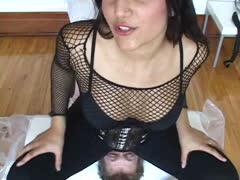 Cruel mistress in boots and fishnets facesits her obedient slave